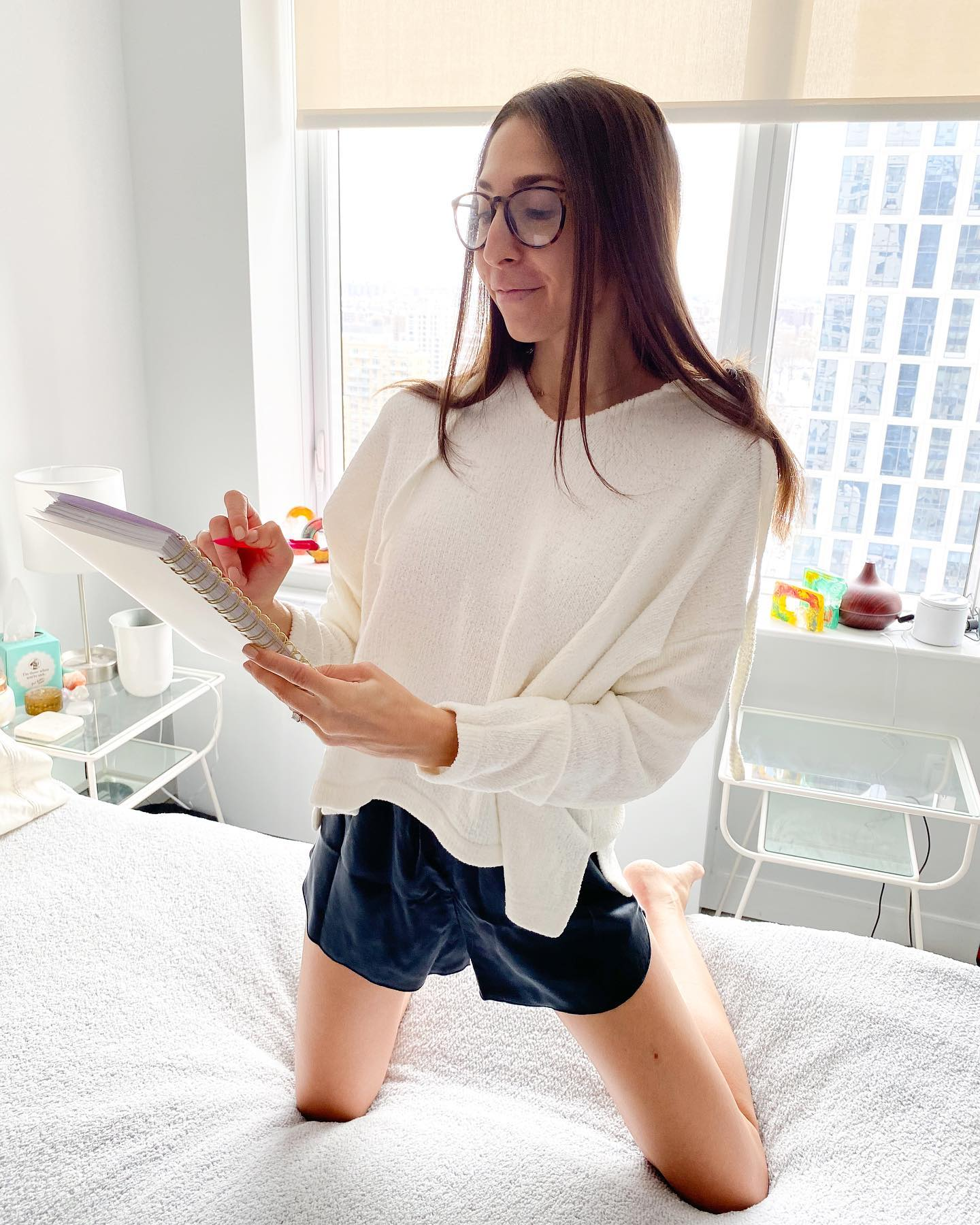 Girl wearing cozy hoodie and writing in journal. Girl journaling in bed. Girl wearing cozy loungewear in bed.