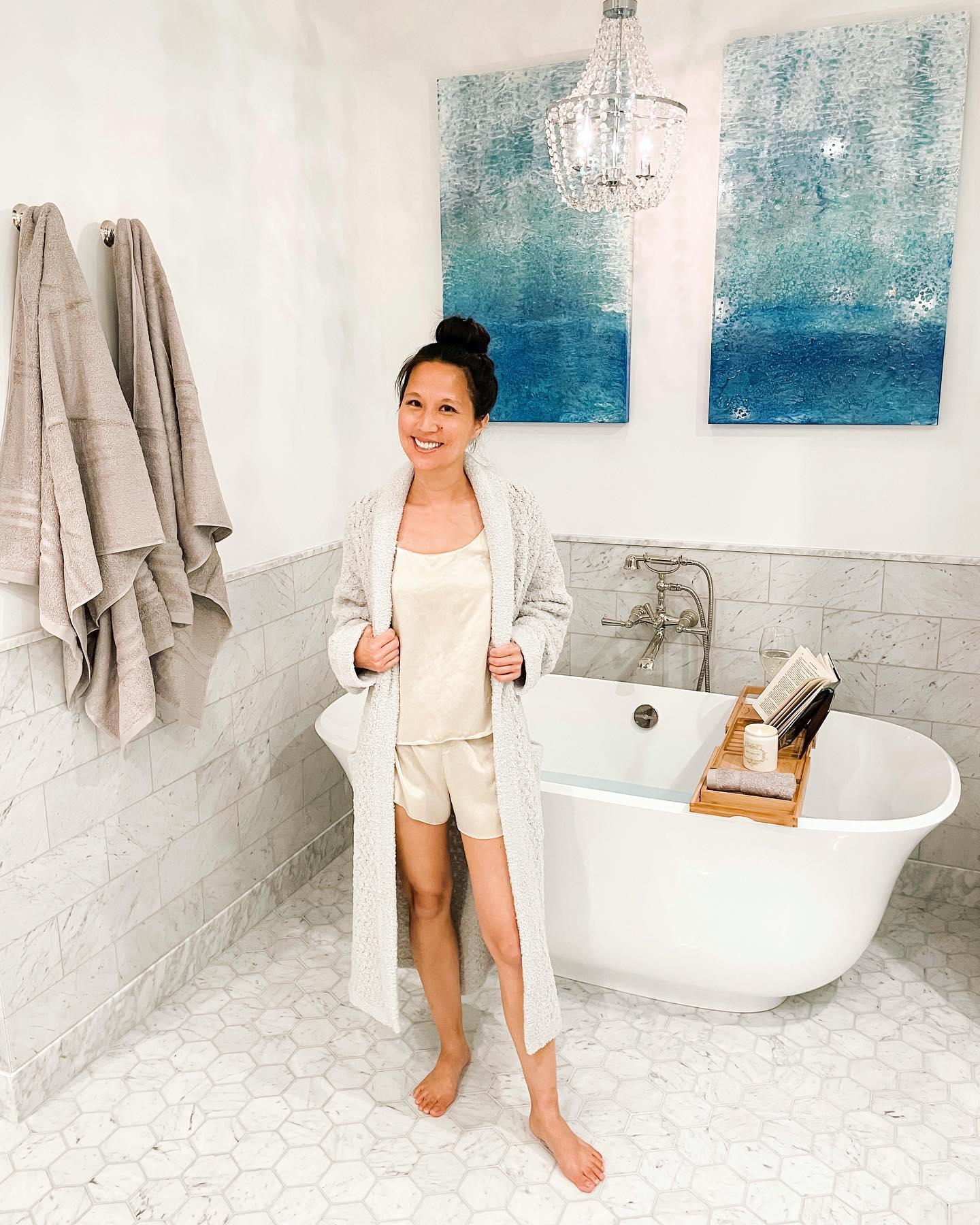Woman standing in bathroom weraing robe. Woman standing near bath tub. Woman standing in pajamas. Woman in bathroom wearing pajamas. Woman wearing pajamas.