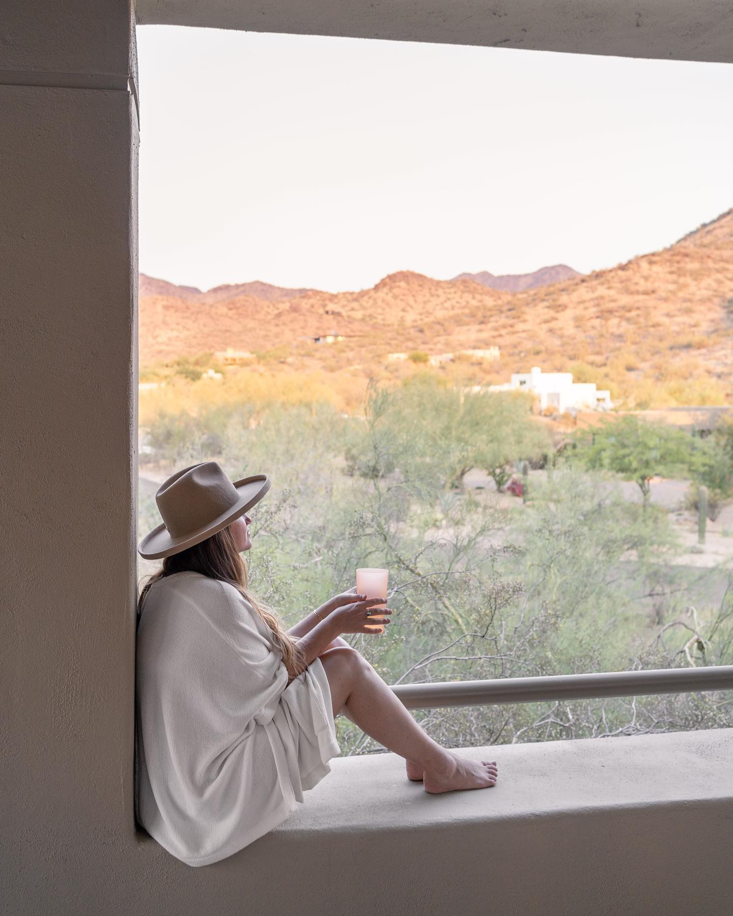Woman looking out into desert. Woman sitting on edge of window drinking wine. Woman wearing hat and poncho. Woman wearing poncho. Woman on vacation in the desert.