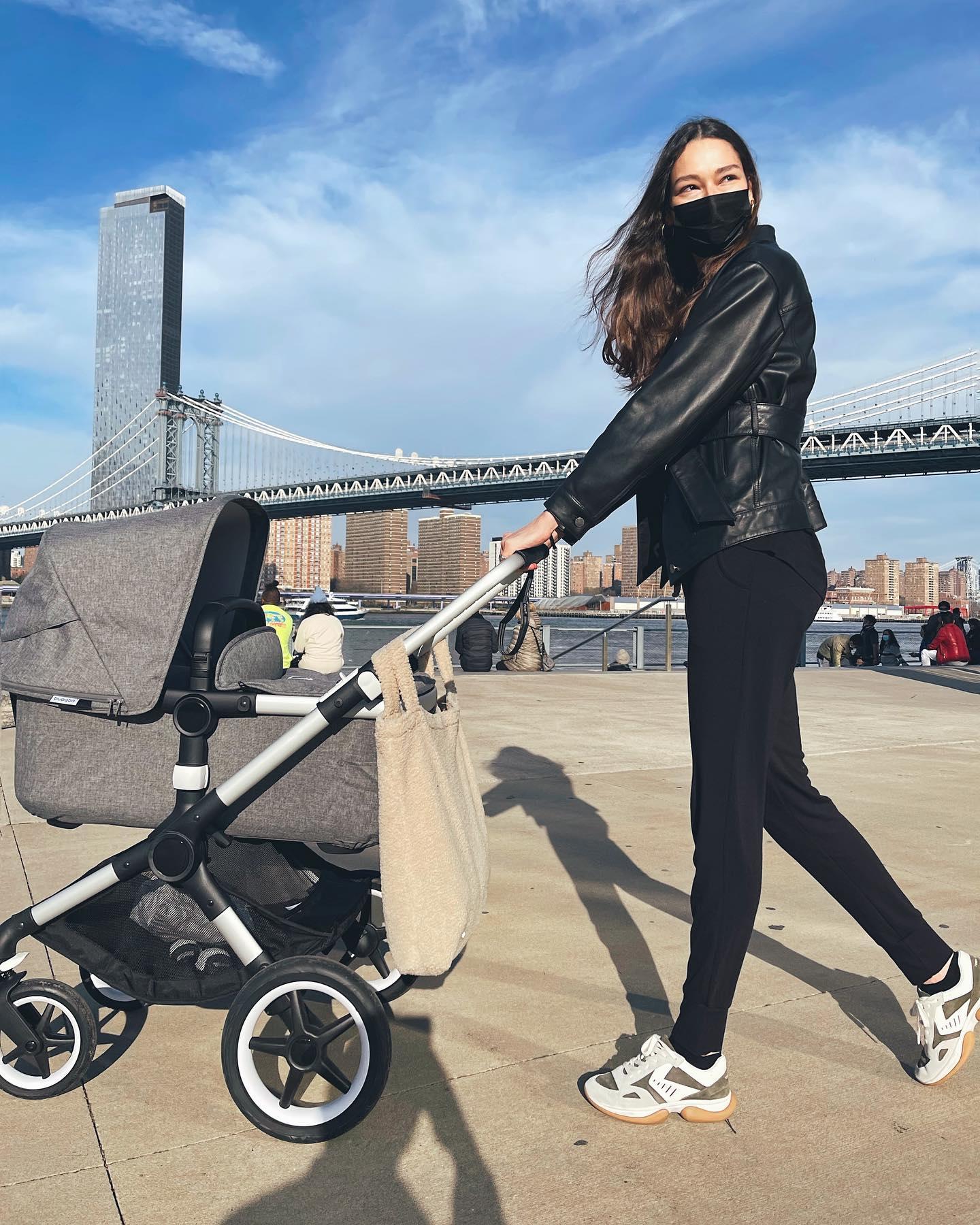 Woman walking baby stroller in New York City. Woman wearing loungewear outside. Woman running errands in NYC.