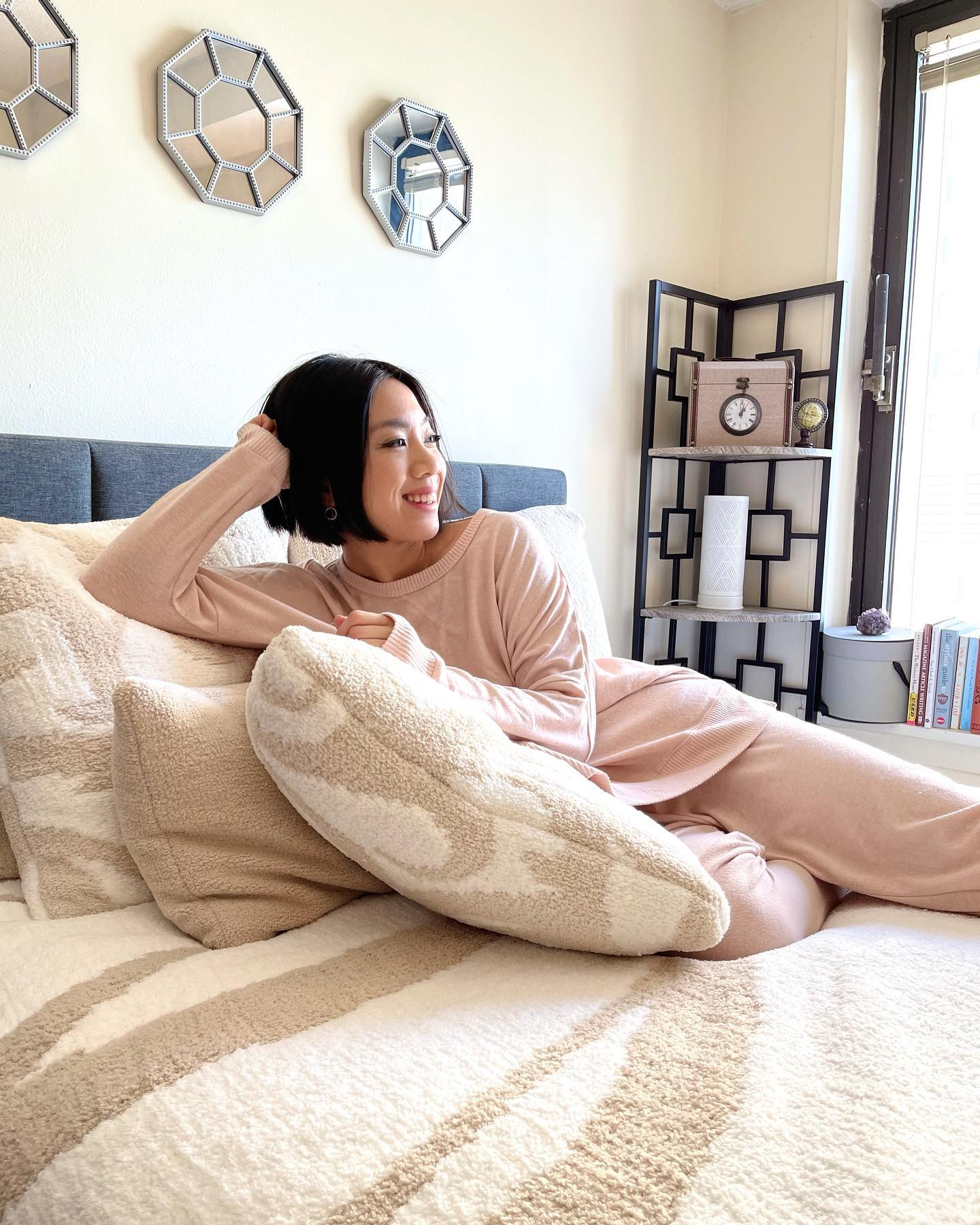 Woman smiling laying on bed. Woman lounging in loungewear. Woman lounging in pajamas. Woman smiling and relaxing on her bed.