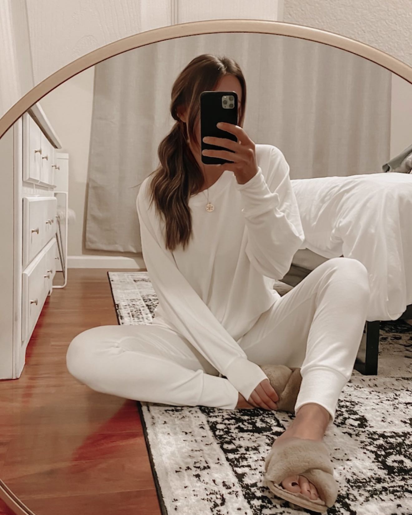Woman taking a mirror selfie with loungewear on. Woman taking mirror pic. Woman wearing loungewear sitting on the floor.